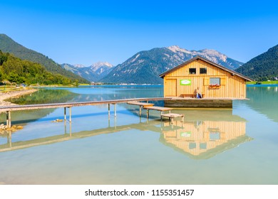 "ACHENSEE LAKE, AUSTRIA - JUL 31, 2018: Wooden boat house and pier of shore of beautiful Achensee lake on sunny summer day. Lake Achensee, also called ""Fjord of the Alps"", is the largest lake in Tyrol."