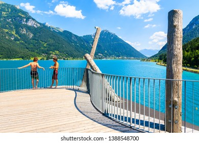 ACHENSEE LAKE, TIROL - JUL 31, 2018: Two young boys preparing to jump off viewpoint platform into beautiful Achensee lake on sunny summer day, Tirol, Austria.