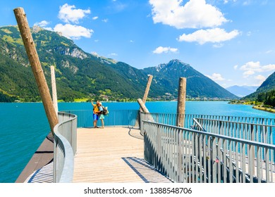 ACHENSEE LAKE, TIROL - JUL 31, 2018: Couple of tourists taking selfie photo on viewpoint platform over beautiful Achensee lake on sunny summer day, Tirol, Austria.