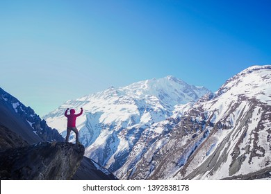 Achiement concept: Man standing and raising hand near clift with mountain scenery