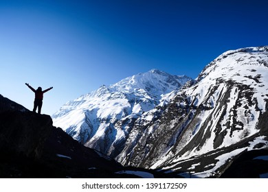 Achiement concept: Woman standing on the edge of a clift while raising hand in Tilicho Base Camp located in Annapurna Circuit