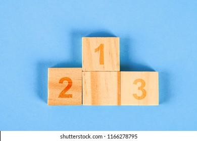 Achievement concept. Wooden podium standing on blue background.