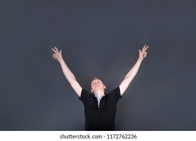 Achievement, success concept. Cheerful blond male raising his hands up, having eyes full of happiness. Attractive male with blonde hair dressed in black t-shirt. Copy space in the top