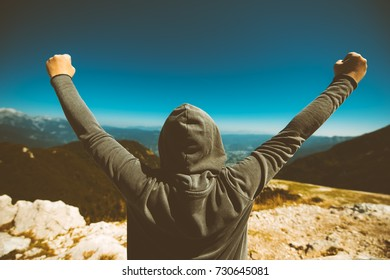 Achievement and triumph. Victorious female person standing on mountain top with arms raised in V. Achievement and accomplishment in life. Toned image.
