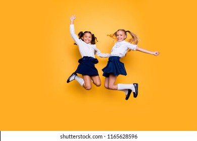 Achievements concept, dynamic images. Full length, legs, body, size portrait of carefree, careless, small girls jumping isolated on yellow background raised fists up