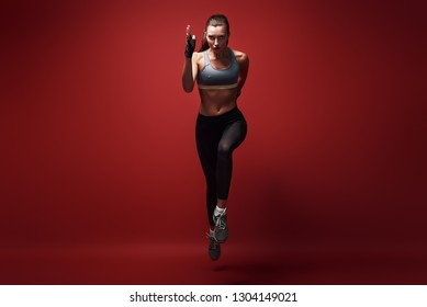 Achieving best results. Young sportswoman sprinting towards camera over red background