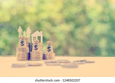 Achieving financial comfort, planning for a secure retirement and mitigating tax expense concept : Family members, house model, dollar bags on coins, depicts saving for wealth / money or income growth