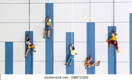 The miniature climbers use a rope to climb the blue bar graph. Achieving goals and competing concepts.