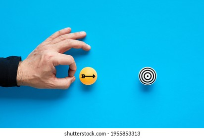 Achieving goals and objectives concept. Male hand is about to flick the ball with arrow icon and shoot the ball with target icon.