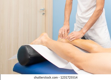 Achilles tendon. The hands of a physiotherapist during a treatment.