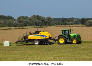 ACHTERHOEK, THE NETHERLANDS - SEP 4, 2012: John Deere 6930 tractor and New Holland BB9060 CropCutter hay baler at work.