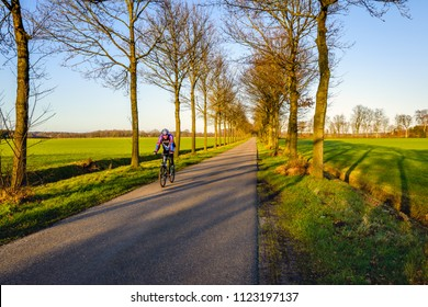 ACHTMAAL, NETHERLANDS, January 28, 2016: Unidentified cyclist bikes alone on a Dutch country road near the village of Achtmaal. On the spot the road  is the border between the Netherlands and Belgium.