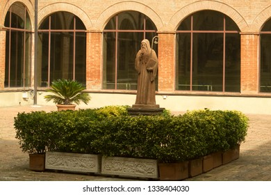 Aciano, Tuscany - Italy, March 7, 2019: Abbey of Monte Oliveto Maggiore:  the statue of Saint Benedict located at the center of cloister