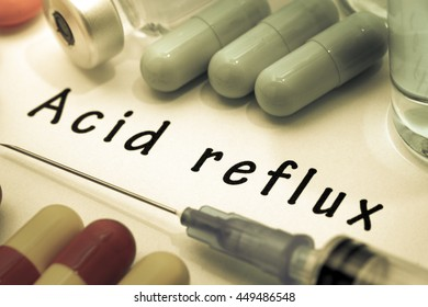 Acid reflux - diagnosis written on a white piece of paper. Syringe and vaccine with drugs. Selective focus