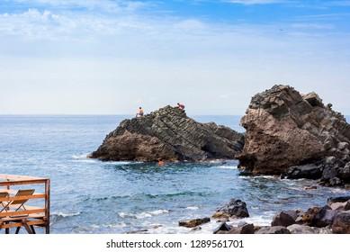 Acitrezza, Catania, Sicily – august 08, 2018: Children swim in the sea near rocks of the Cyclops, sea stacks in Acitrezza, Italy