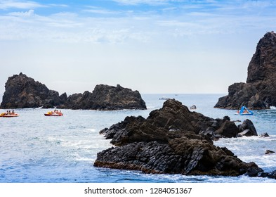 Acitrezza, Catania, Sicily – august 8, 2018: people boating and swimming in the sea near the rocks of the Cyclops