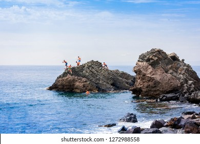 Acitrezza, Catania, Sicily, Italy – august 08, 2018: children plunge into the sea next to Cyclops islands