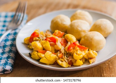 Ackee and Salt fish served with fried dumplings and served on a white plate