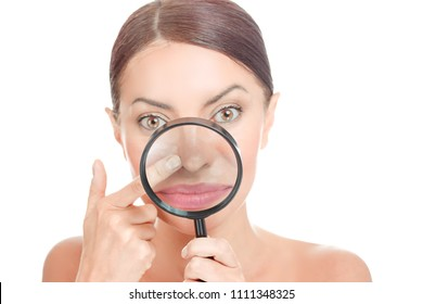Acne blackheads on woman's nose showed in a magnifying glass, facial scar, skin problem, beauty concept. Girl holding magnifier to show bumpy skin, clog pores, which appears to be clean. Focus on nose