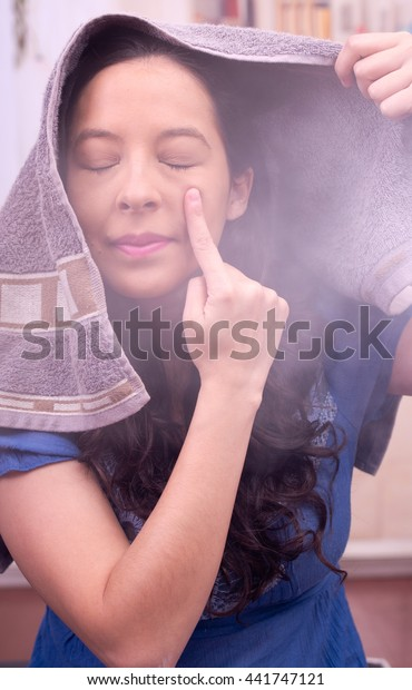 Acne is common in young womans, steam treatment to clean the face, finger covering