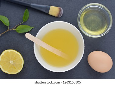 Acne skin treatment, homemade facial mask with egg white and lemon juice, flat lay with ingredients on black background.