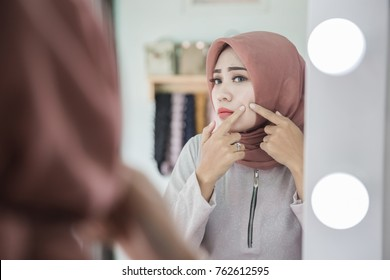 Acne treatment. Acne woman. Young muslim woman squeezing her pimple, removing pimple from her face