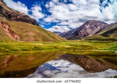 Aconcagua, the highest peak in South America reflected in small pond on a trail to the summit, Argentina