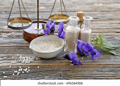 Aconitum napellus in homeopathy medicine with vintage bottles , scales on wooden