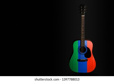 Acoustic concert guitar with a drawn flag Dagestan, on a dark background, as a symbol of national creativity or folk song. Horizontal frame