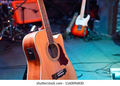 Acoustic and electric guitar and other musical equipment on stag