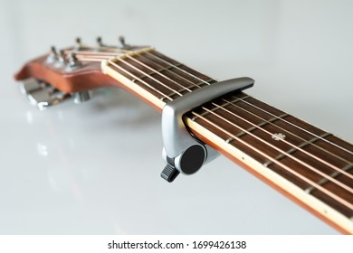 Acoustic guitar with capo on the third fret