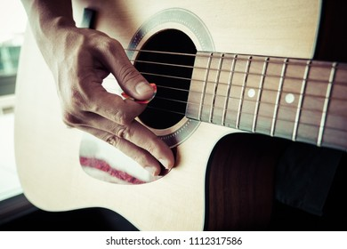 acoustic guitar close-up playing for folk music, process color.