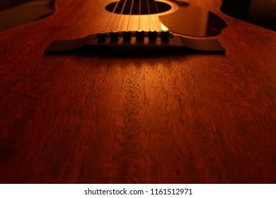 Acoustic guitar fixed guitar top/bridge close-up showing mahogany open pore wood grain