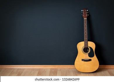 Acoustic guitar leaning on black wall