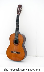 acoustic guitar leaning on a white wall