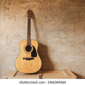 Acoustic guitar leans against the wall, on music instrument wooden box, shadow casting on concrete wall in day time.
