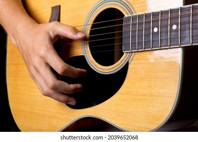 Acoustic guitar and man's hand strumming guitar chords close up photo