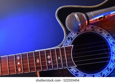 Acoustic guitar and microphone isolated with red and blue lights. Top view. Horizontal composition.