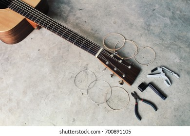 An acoustic guitar with new set of strings and tools for changing guitar strings.