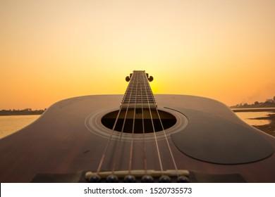 Acoustic guitar on the beach against sunset