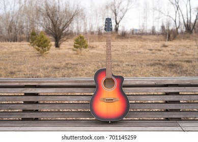 Acoustic guitar on a bench outdoors in the park
