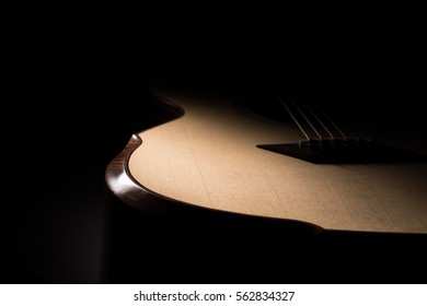 Acoustic guitar on black background.