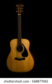 Acoustic guitar on black background with copy space