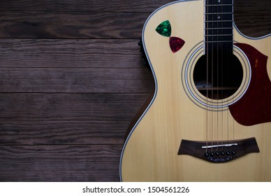 Acoustic guitar on an old wooden table, See only the acoustic guitar body, Close-up, Copy-space.
