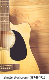 Acoustic guitar on wood background.