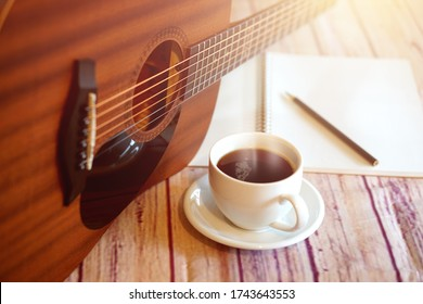 Acoustic guitar placed with a coffee cup, notebook and pencil placed on a wooden floor.