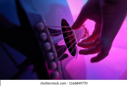 Acoustic guitar played by a girl and colorful lights