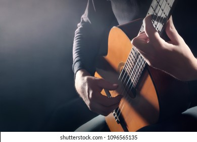 Acoustic guitar player. Classical guitarist hands playing music instrument closeup