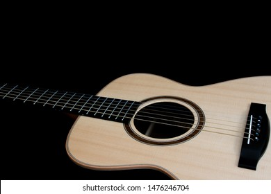 Acoustic guitar. Singer songwriter steel string folk guitarist musical instrument close-up on black background with copy-space. High quality spruce wood top with ebony fingerboard and bridge.