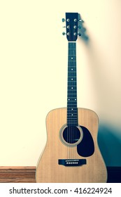 Acoustic guitar standing against white wall background.